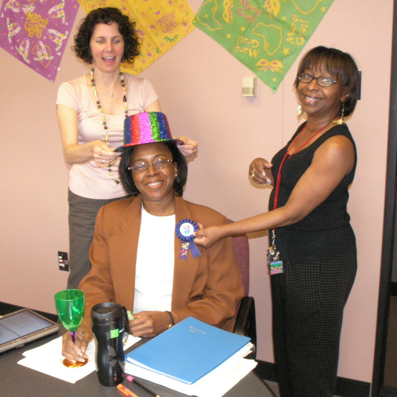 A pair of coworkers put a colorful party hat and ribbon on a colleague as part of an office birthday celebration.