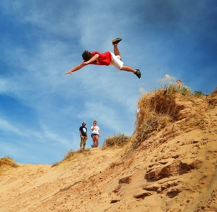 A young man jumps head first off the top of a sand dune and down a steep slope.
