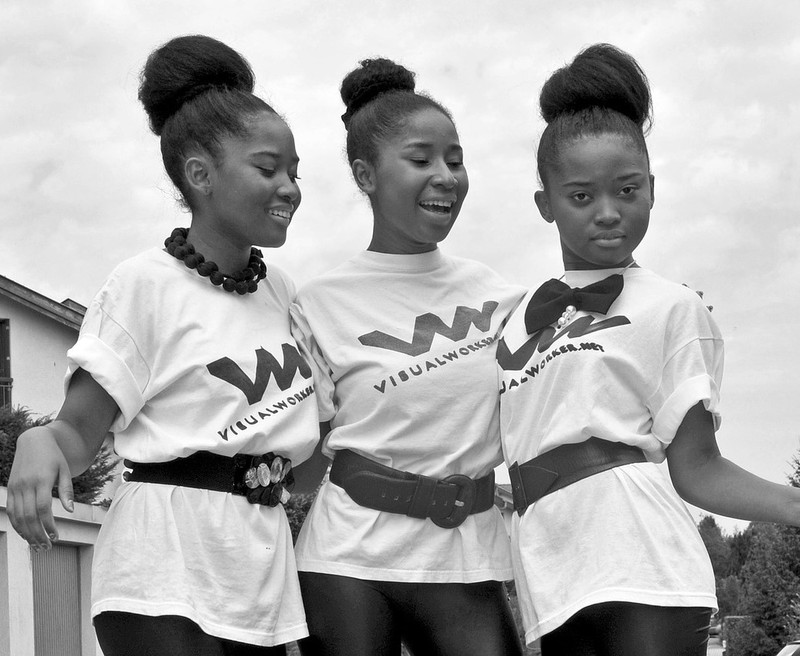 A group of teen girls with matching shirts and hair styles pose together with their arms around one another.