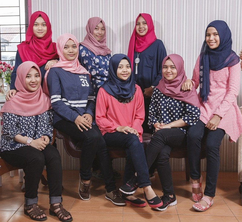 A group of Malaysian teen girls pose for a photo wearing casual clothing and traditional head scarves.