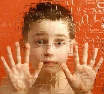 A young boy looks out from behind textured glass.