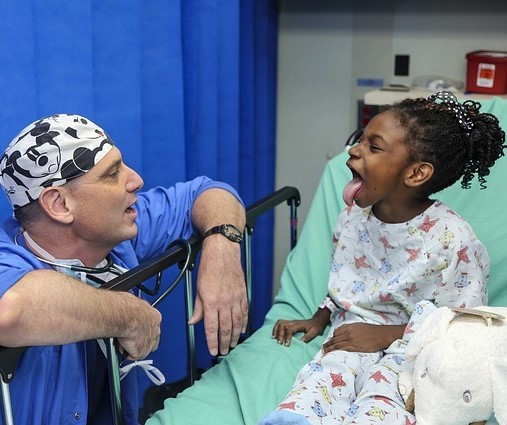 A doctor visits a young patient in a hospital bed. She playfully sticks her tongue out to show the doctor.