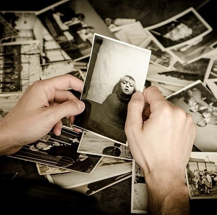 Hands sifting through a box of old photographs.