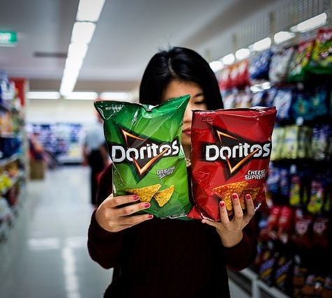 A woman in a supermarket aisle holds two different types of Doritos and carefully reads the packages.
