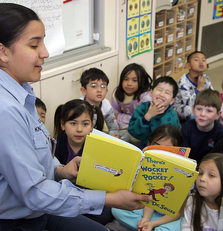 A teacher reads a story to a group of grade school students.