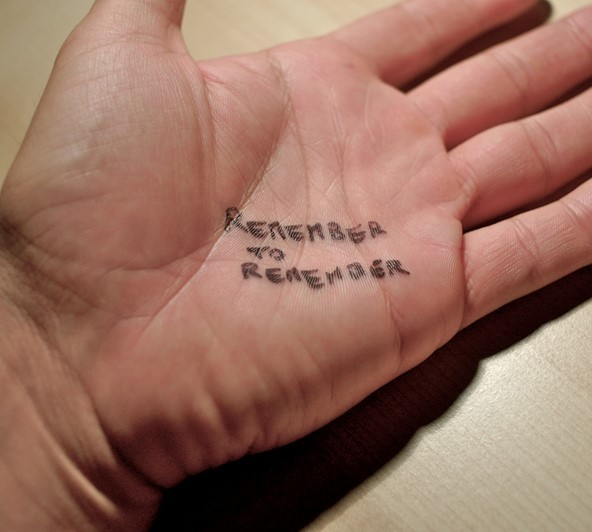 "A note is written on a man's hand which says, ""remember to remember""."