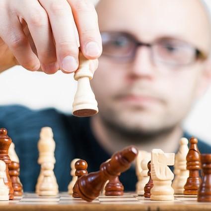 A man makes a chess move.