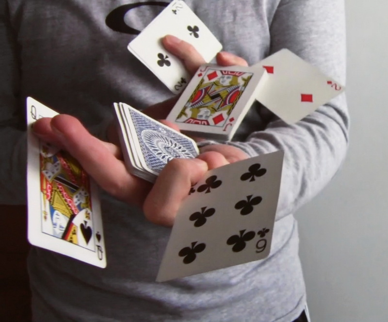 A magician manipulates a deck of cards.