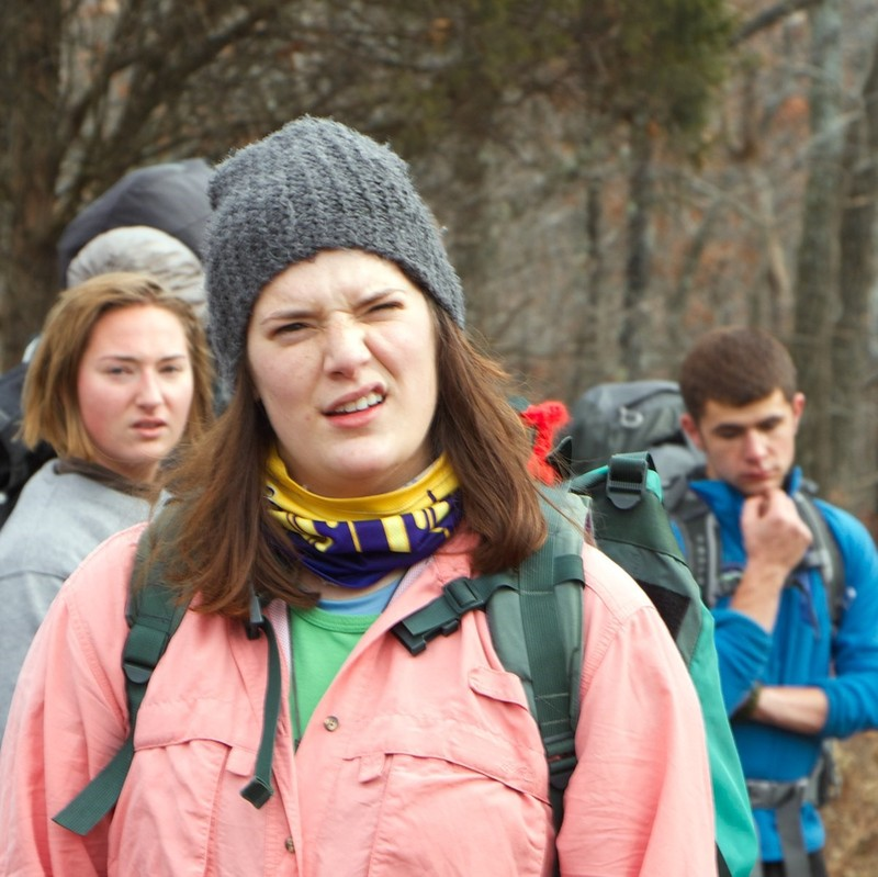 A group of hikers are stopped in the middle of a trail with confused looks on their faces.