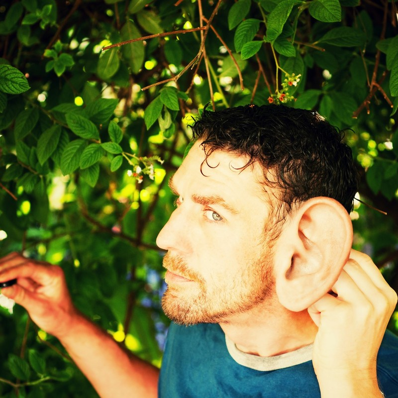 A man puts his hand behind his unusually large ear as if trying to locate the location of a sound.