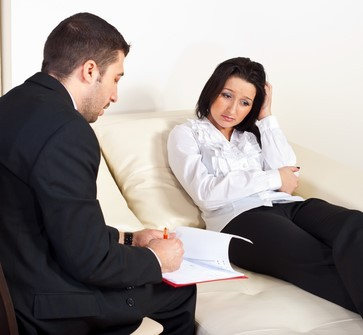 A clinical psychologist meets with a client during an office visit.