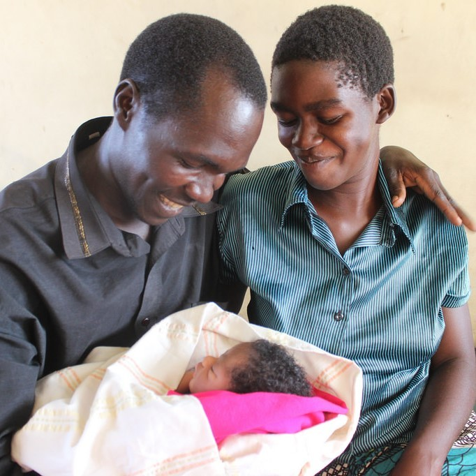 A young mother and father are all smiles as they hold their infant.