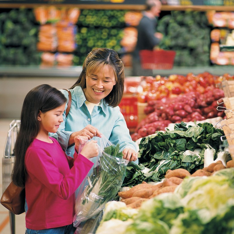 A mother and daughter shopping for vegetables at the supermarket.