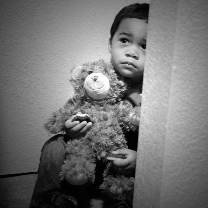 An unhappy looking little boy sits with his teddy bear on the floor of a closet.