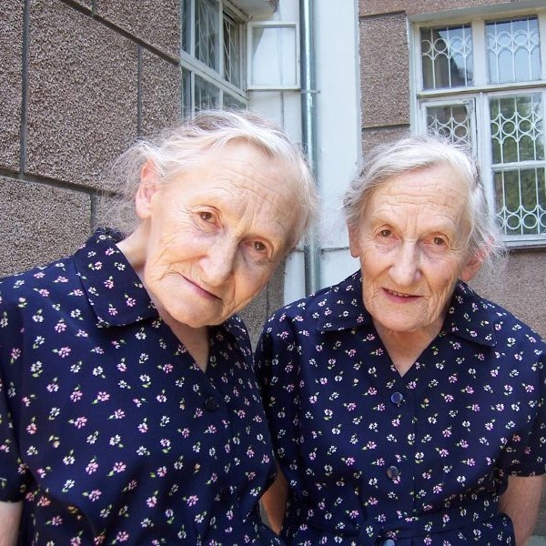 75-year old identical twins wearing identical dresses.