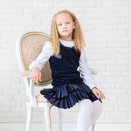 A young girl poses for a portrait dressed in an outfit that society might generally considered appropriately feminine - white tights, pleated velvet skirt, ruffled collar, and tailored cuff.