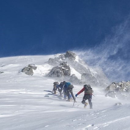 A group of mountaineers climbing to a snowy summit.