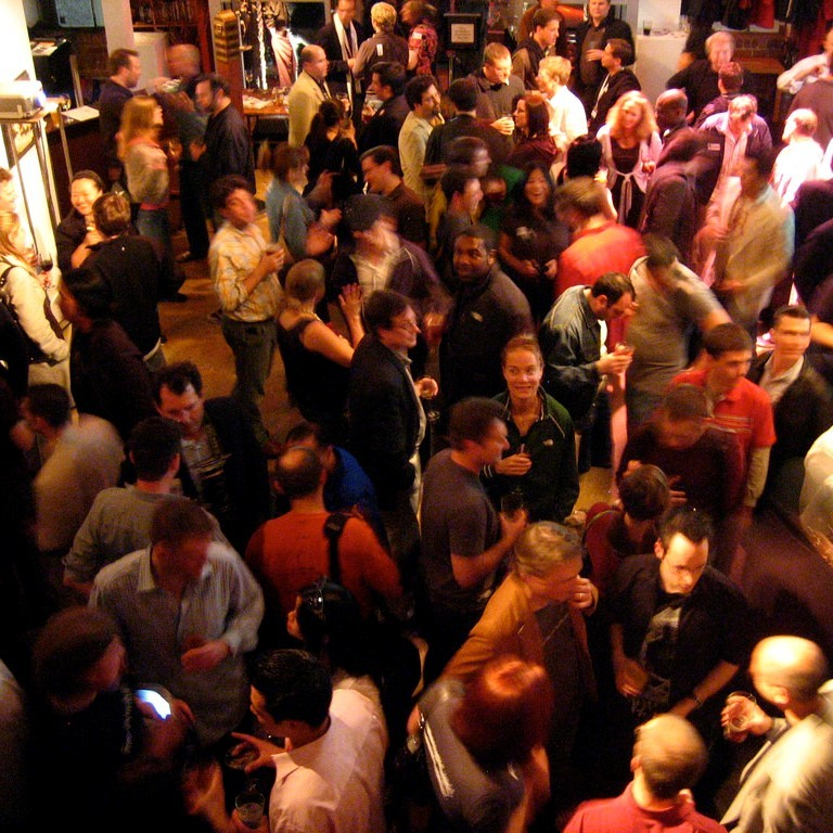 People stand and talk in groups of 3 or 4 during a party.