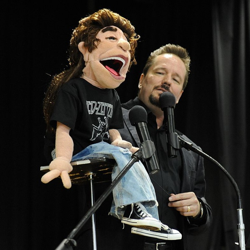 A ventriloquist performs on stage.
