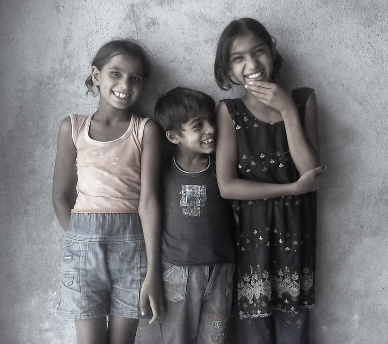 Three smiling siblings.