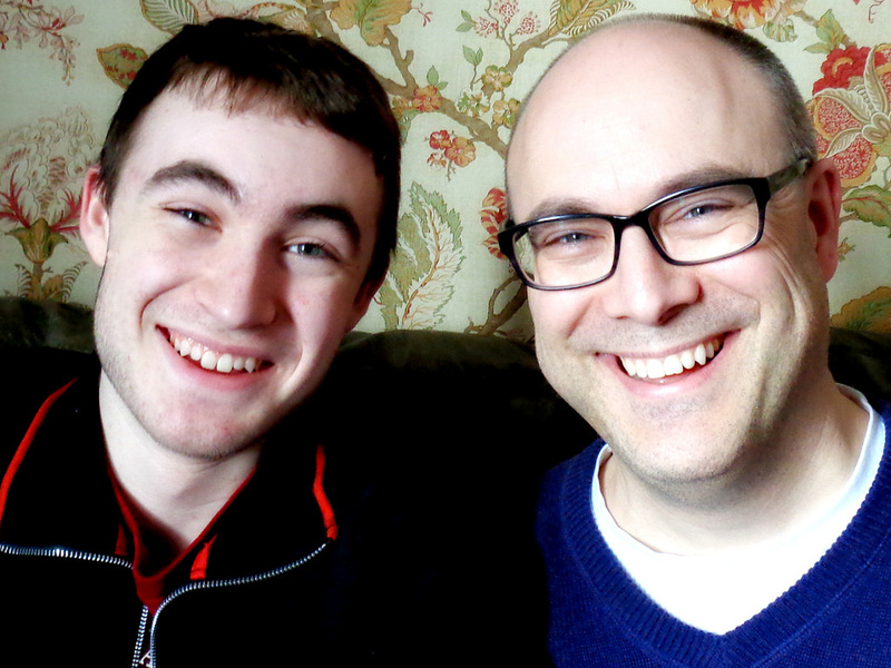 A teen son and his father with a strong family resemblance.