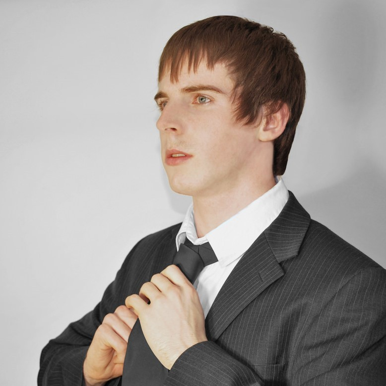 A young man in a suit adjusts his tie.