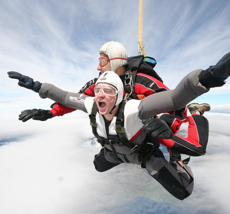 A man yells with excitement during a tandem skydive.