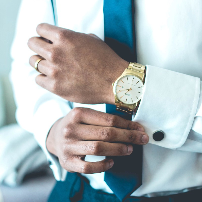A man dressed in business attire and an expensive watch adjusts his cufflinks.