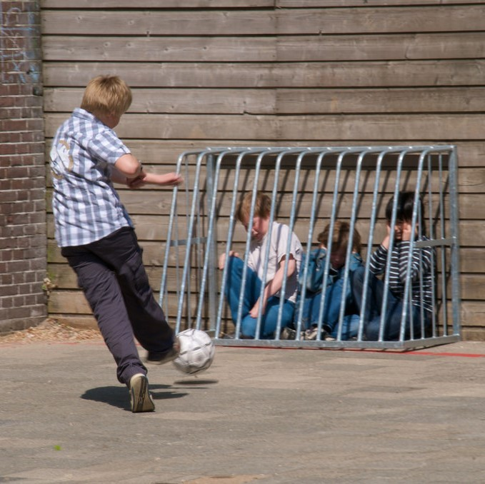 A playground bully kicks a soccer ball at a group of students huddled behind a barrier.
