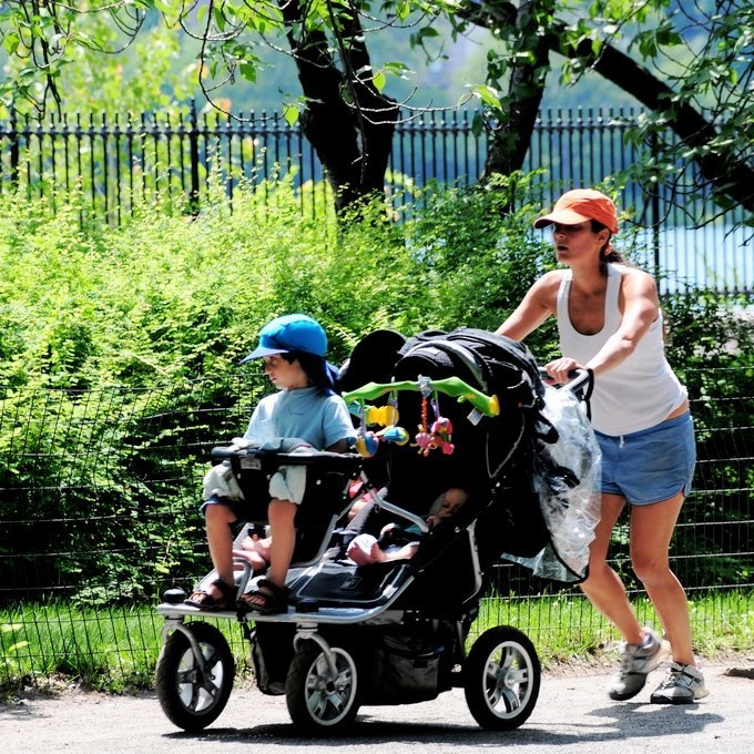A woman jogs through a park with three young children in a stroller.