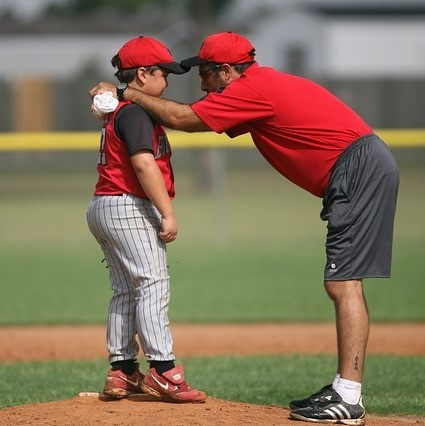 A baseball coach gives encouragement to a little league pitcher as they stand together on the mound.
