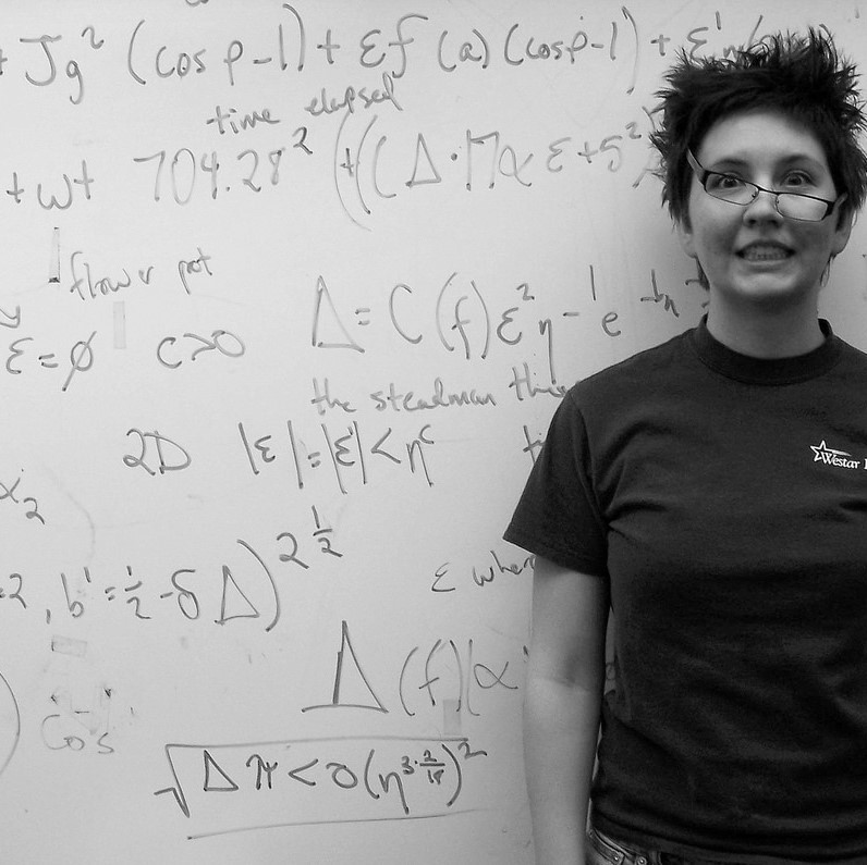 A woman stands triumphant but slightly disheveled after solving a complicated math problem on the whiteboard.