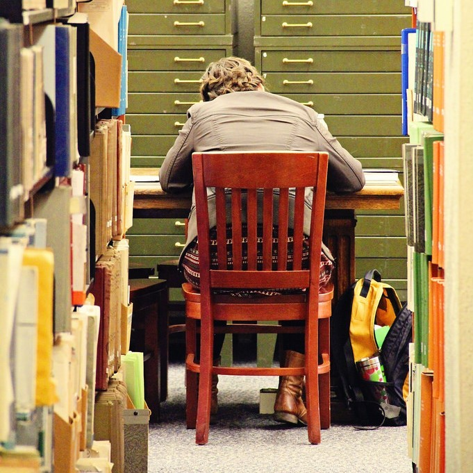 A student is hunched over a desk in the library.