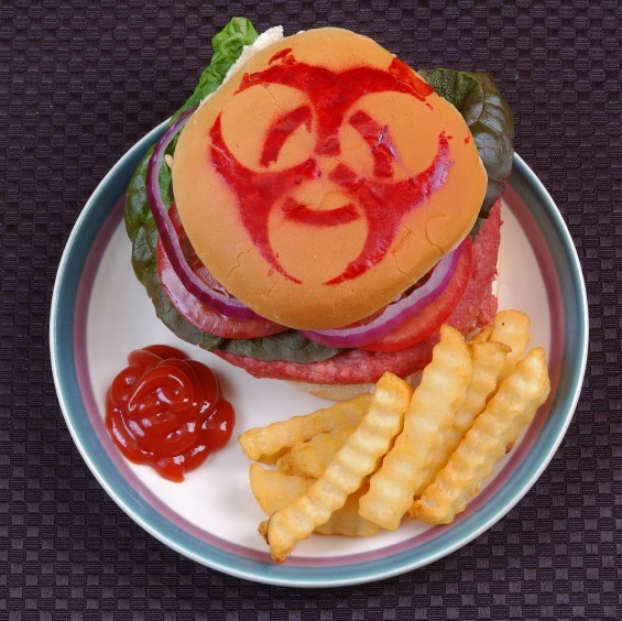 A hamburger with a bio-hazard symbol drawn on the bun with ketchup.