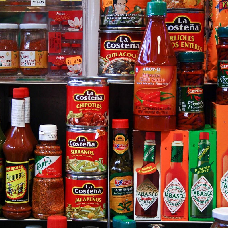 A selection of canned peppers and hot sauces on a supermarket shelf.