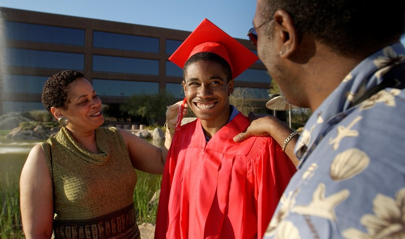 Smiling parents stand with their young adult son who is dressed in a graduation cap and gown.