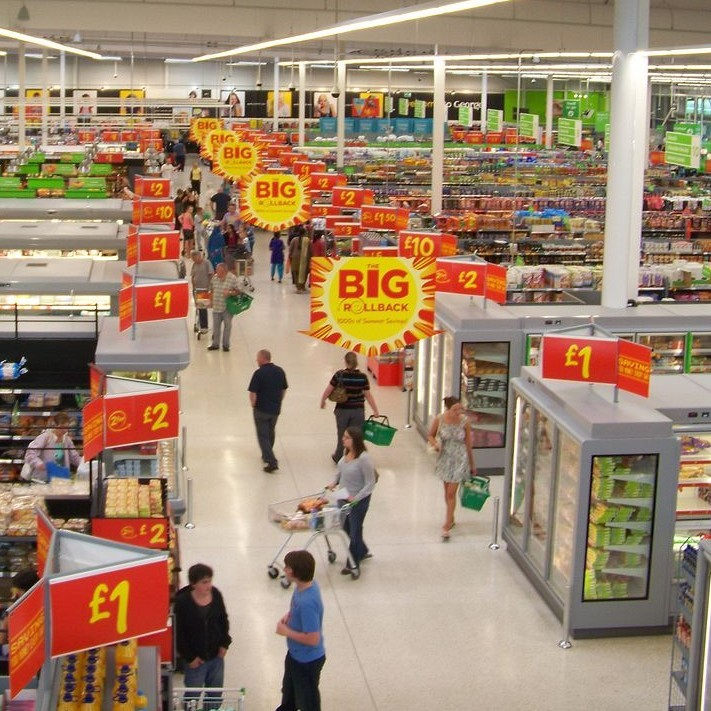 View of a modern supermarket with many aisles full of thousands of products and many hundreds of bright signs with product information.