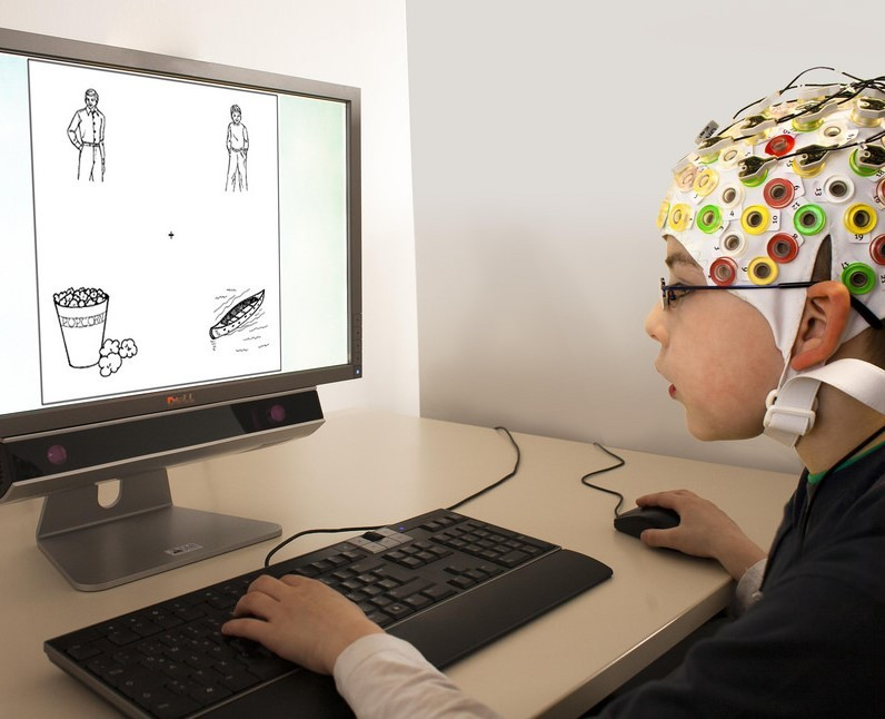 A boy wearing an EEG cap uses a mouse and keyboard while looking at images on a computer monitor during an experiment.