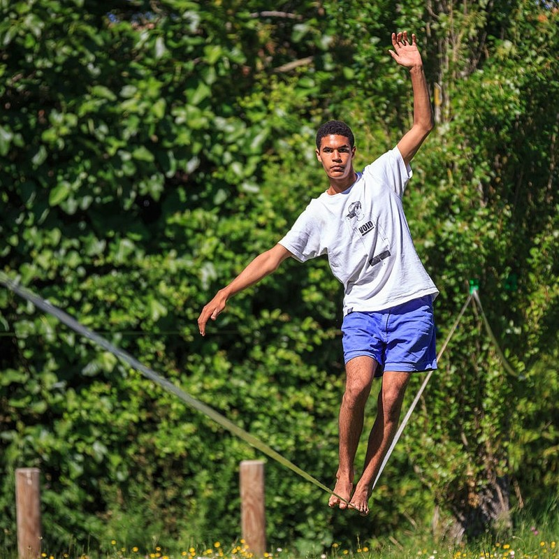 A man walks across a slackline with his arms extended for balance.