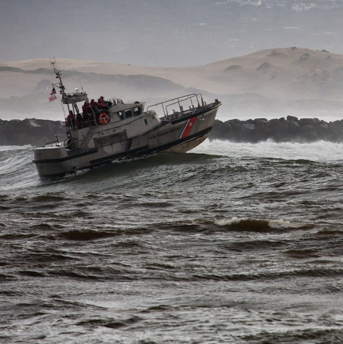 A small coast guard ship moves through large ocean waves.