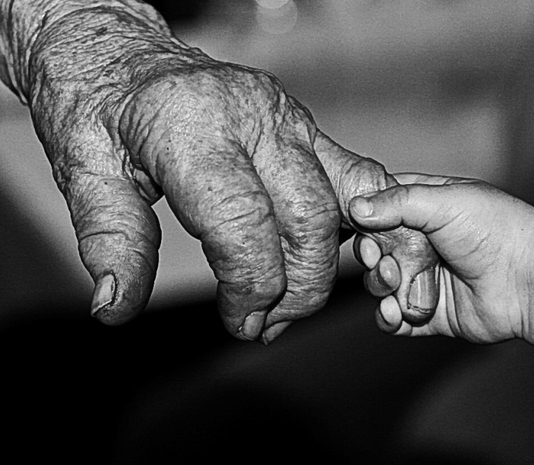 A very small hand of a child holds a wrinkled finger on the hand of a very old person.