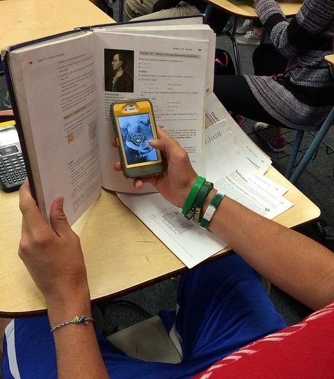 A student sits at a desk using a cell phone hidden behind a textbook.