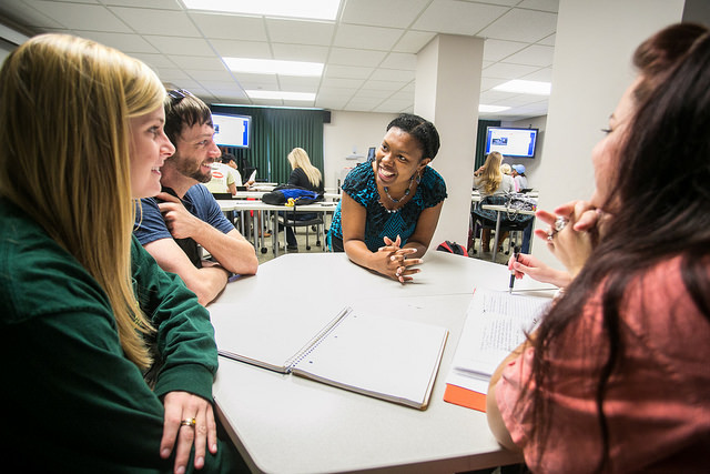 An instructor enjoys a discussion with a group of students during a class.