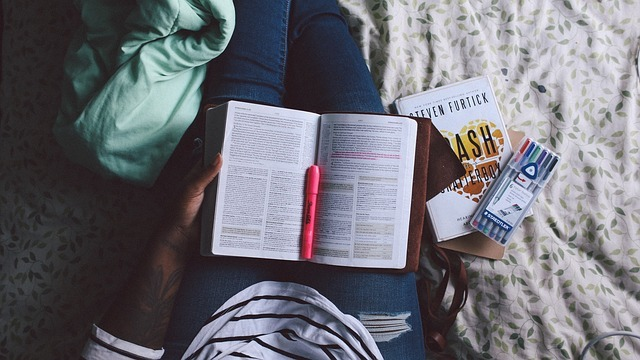 A student sits with an open book in her lap and a set of highlight markers close by.