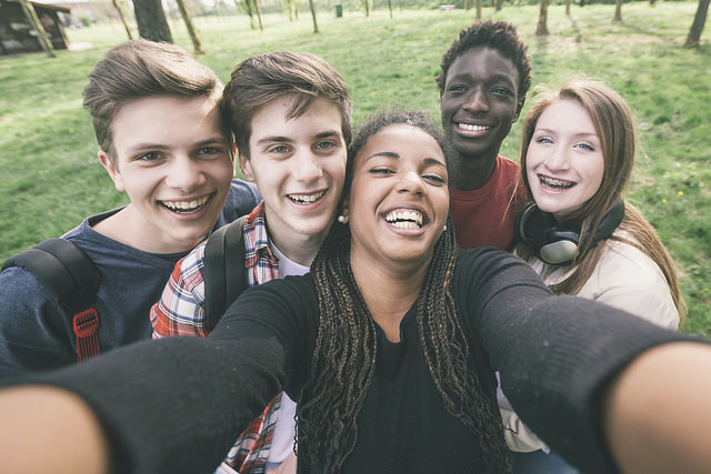 A group of Generation Z students pose for a group selfie.
