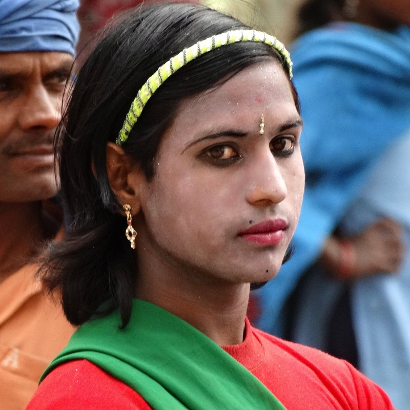 A hijra dancer with a feminine appearance wearing eyeliner, lipstick, and earrings.