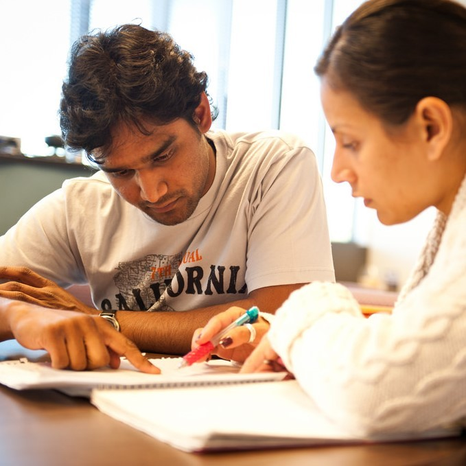 A male and female student work together at a table and focus on details in a notebook in front of them.