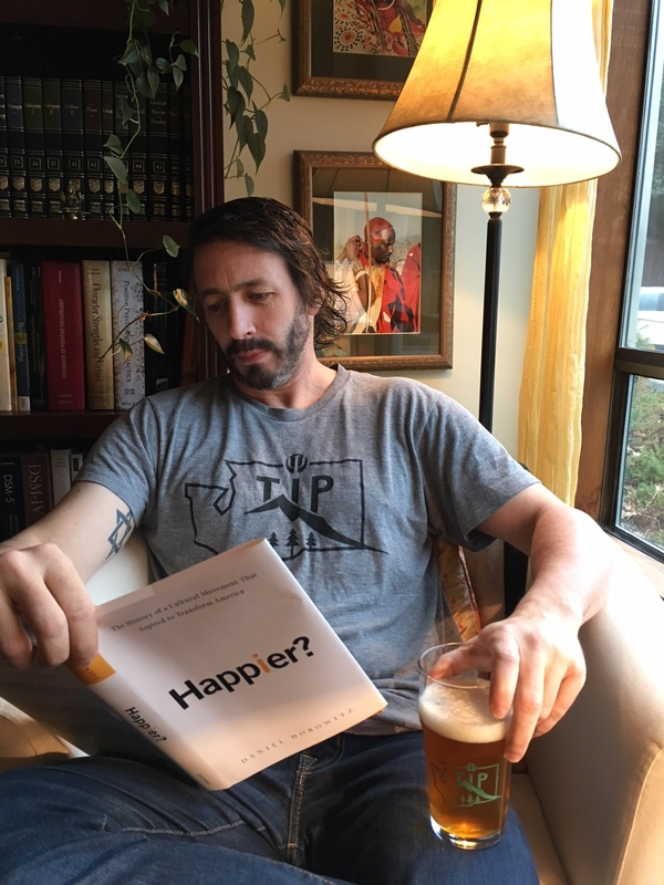 Noba editor Robert Biswas-Diener wearing a TIP NW t-shirt and holding a TIP NW pint glass.