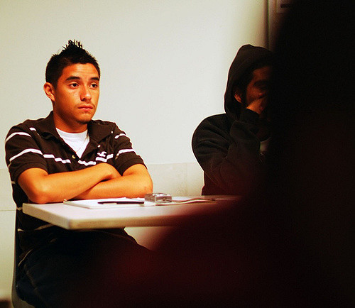 A student sits in the back of a classroom with his arms folded and a blank stare on his face.