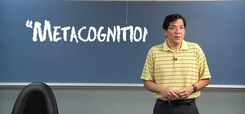 Dr. Chew stands in front of a board in a classroom with the word 'metacognition' written on it.